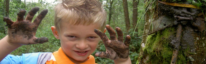 A boy with muddy hands enjoys a hands-on educational visit
